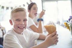 Kinderen die roomijs van kegels genieten bij een roomijswoonkamer royalty-vrije stock afbeelding