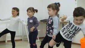 Kinderen ` die s een spelruimte ontwikkelen Emoties van jonge kinderen tijdens het onderhouden klassen De kerelstribune in lijn stock footage