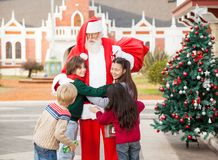 Kinderen die Santa Claus omhelzen Stock Fotografie
