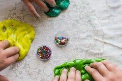 Kinderen die slijm in hun handen met klatergoud houden stock foto