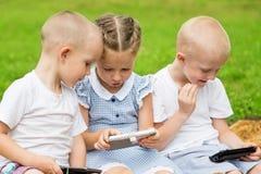 Kinderen die smartphones zitting op het gras gebruiken Royalty-vrije Stock Fotografie