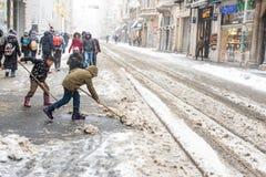 Kinderen die sneeuw van populaire Istiklal-Straat van Beyoglu schoonmaken Royalty-vrije Stock Afbeelding