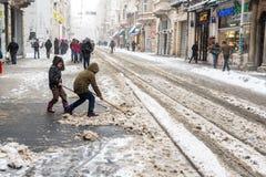 Kinderen die sneeuw van populaire Istiklal-Straat van Beyoglu schoonmaken Stock Fotografie