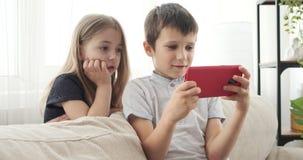 Kinderen die spel op smartphone spelen stock video