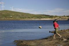 Kinderen die stenen werpen aan het pond stock afbeeldingen