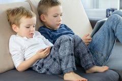 Kinderen die tabletcomputer met behulp van Broers die op laag bij de woonkamer zitten en met tabletapparaat spelen royalty-vrije stock fotografie