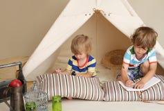 Kinderen die thuis binnen met een tipitent spelen stock foto's