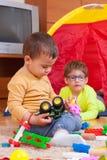 Kinderen die thuis spelen Stock Foto's