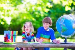 Kinderen die thuiswerk in schoolwerf doen Royalty-vrije Stock Afbeelding