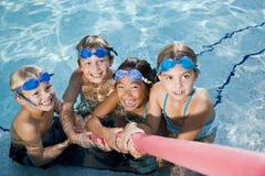 Kinderen die touwtrekwedstrijd in pool spelen royalty-vrije stock foto's