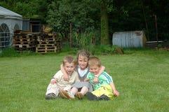 Kinderen die in tuin spelen. stock afbeeldingen