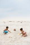 Kinderen die vader in zand begraven royalty-vrije stock afbeelding
