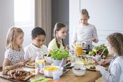 Kinderen die van een gezonde maaltijd genieten door een lijst in een eetkamer dur stock afbeeldingen