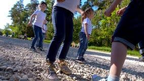 Kinderen die voetbalvoetbal in openlucht in de zomerdag spelen onder de slow-motion zon, stock footage