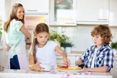 Kinderen die vruchtencake met rode aalbessen bakken Stock Fotografie