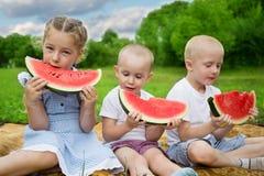 Kinderen die watermeloenzitting op het gras eten Royalty-vrije Stock Foto