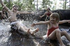 Kinderen die in waterval spelen Stock Afbeeldingen