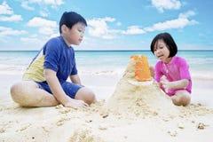 Kinderen die zand spelen bij kust Stock Fotografie