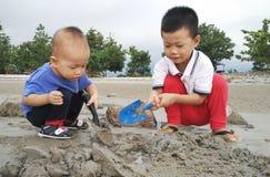 Kinderen die zand spelen bij strand Stock Afbeelding