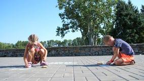 Kinderen, een jongen en een meisje in zonnebril, verf met kleurpotloden op het asfalt, straattegels Een hete de zomerdag stock videobeelden