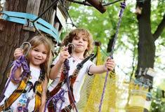 Kinderen - een jongen en een meisje in de de pashindernissen van het kabelpark Stock Afbeeldingen