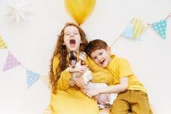 Kinderen en hun hond die omhelst en een lied voor zijn geboorte zingen stock foto's