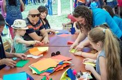 Kinderen en hun ouders die op kunsten en ambacht in openlucht workshop deelnemen stock foto's