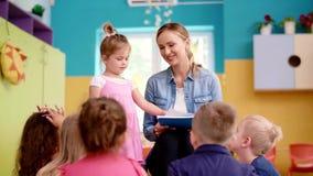 Kinderen en leraar in de kleuterschool stock videobeelden