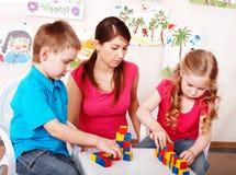 Kinderen en leraar met houtsnede in kleuterschool. Stock Afbeeldingen
