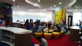 Kinderen en ouders in de ruimte van de kinderenbibliotheek stock footage