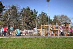 Kinderen en ouders in motie het spelen in het park Stock Afbeelding