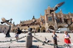Kinderen en toeristen bij vierkant in Krakau Polen Stock Foto