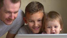 Kinderen en vader de horlogevideo op laptop, glimlach, heeft pret stock videobeelden