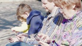 Kinderen en volwassenen met mobiele telefoons, familiemededeling stock videobeelden