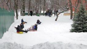Kinderen en volwassenen op een opblaasbare slee en een buis Ijzige sneeuwheuvel buizenstelsel Rusland, stad van Saratov, 10 Janua stock footage