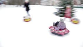 Kinderen en volwassenen op een opblaasbare slee en een buis Ijzige sneeuwheuvel buizenstelsel Rusland, stad van Saratov, 10 Janua stock videobeelden