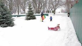 Kinderen en volwassenen op een opblaasbare slee en een buis Ijzige sneeuwheuvel buizenstelsel Rusland, stad van Saratov, 10 Janua stock video