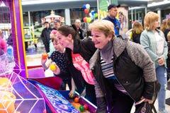 Kinderen en volwassenenspel op de gokautomaten, aantrekkelijkheden in het winkelcentrum De families met kinderen hebben pret en s stock fotografie