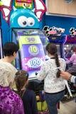 Kinderen en volwassenenspel op de gokautomaten, aantrekkelijkheden in het winkelcentrum De families met kinderen hebben pret en s royalty-vrije stock afbeelding