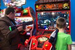 Kinderen en volwassenenspel op de gokautomaten, aantrekkelijkheden in het winkelcentrum De families met kinderen hebben pret en s royalty-vrije stock foto's