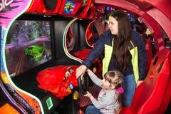 Kinderen en volwassenenspel op de gokautomaten, aantrekkelijkheden in het winkelcentrum De families met kinderen hebben pret en s stock afbeeldingen