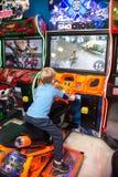 Kinderen en volwassenenspel op de gokautomaten, aantrekkelijkheden in het winkelcentrum De families met kinderen hebben pret en s stock foto