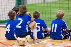 Kinderen futsal team Groep jonge binnenvoetballers die samen zitten stock afbeelding