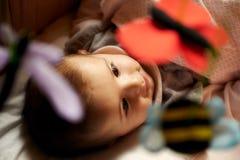 Mooi weinig vrouwelijke baby die en met dierlijk stuk speelgoed glimlachen spelen Royalty-vrije Stock Foto