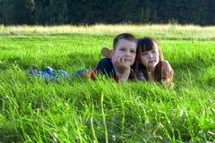 Kinderen in gras Stock Afbeeldingen