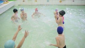 Kinderen hebben plezier in het zwembad Kinderen spatten water, maken een spray van water in het zwembad in de kleuterschool stock footage