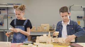 Kinderen het bezige spelen op ambachtworkshop Leuk weinig jongen en zijn school-verouderde zuster die met houten half afgewerkt s stock videobeelden