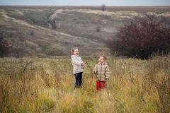Kinderen in het gebied in werking dat worden gesteld dat De kinderen spelen op het gebied bij het gouden uur royalty-vrije stock foto's
