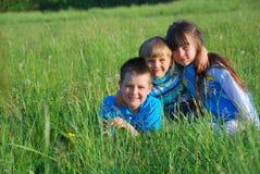 Kinderen in het gras Stock Afbeeldingen