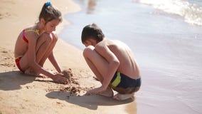 Kinderen jongen en meisjes het spelen met zand op het strand bouw een zandkasteel stock footage